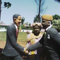 statue at Kogelo village resort painting a fictional meeting between Mama Sarah Obama, Barack and Luo political scion Raila Odinga.jpg